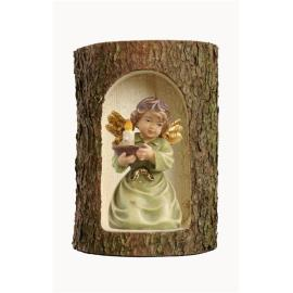 Bell angel with candle-carrier in a tree trunk